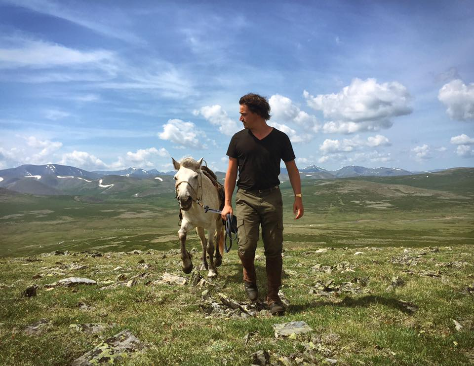 Erik Cooper leading horse Mongolia